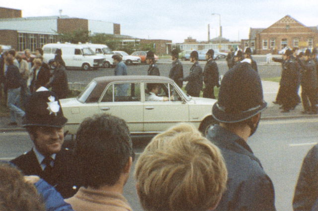 A smiling bobby and marching police move pickets on outside Harworth Colliery entrance.