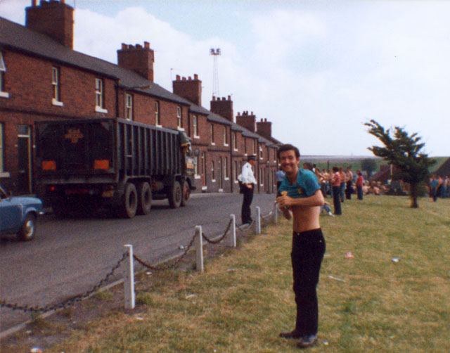 "Darren ""Daz"" Goulty near the entrance to Newstead Colliery. The police officer from Welwyn garden City with hands on hips and an NCB coal lorry, a legitimate target. Pickets in the background near the pit entrance."