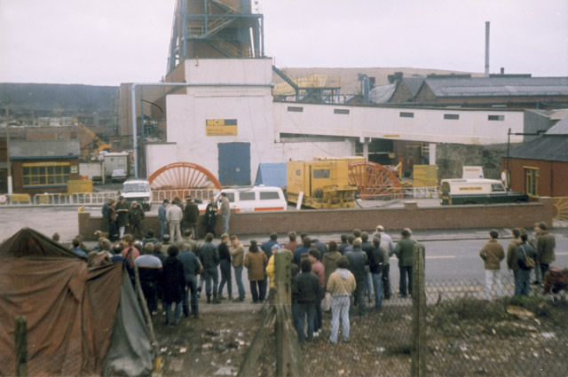 Silverwood Colliery. 'The official picket' stood next to the wall at the pit entrance. Some lads put a tarpaulin up, with a nice brazier next to it.