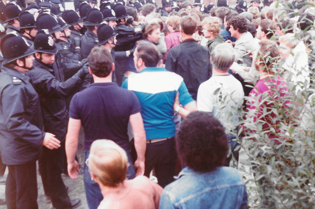 Police warning striking miner. Top, middle of photo, striking miner attempts to escape from police clutches.