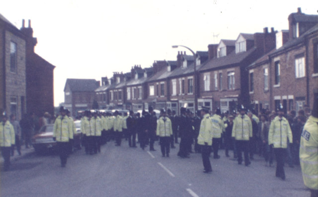 Shireoaks, October 16th. The police out in force. 'Snatch Squad' followed by uniformed police. We were forced marched up the road by police in fluorescent jackets. No identification numbers and all big buggers. Commanding officer wearing flat hat, middle right.