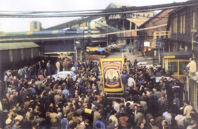 Silverwood banner in the pit yard at the end of the March back to work. 9.00am, Tuesday 5th March 1985. Top right. Management wearing suits head towards the scabs looking on, instructing them to get out of sight.