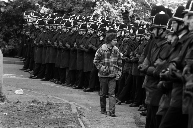 Defiant: Striking miner walking past massed ranks of police at Orgreave in 1984